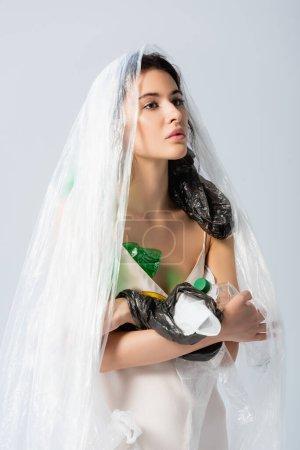 Photo pour Femme brune avec sac en plastique sur la tête debout en robe de soie avec des bouteilles vides isolées sur blanc, concept écologie - image libre de droit