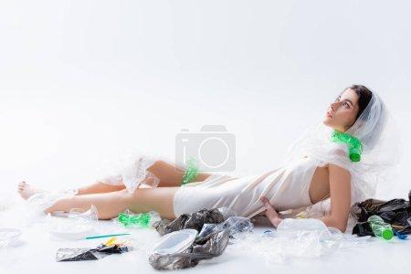 Photo pour Jeune femme pieds nus en robe de soie avec sac en plastique sur la tête assise près de bouteilles vides sur blanc, concept d'écologie - image libre de droit