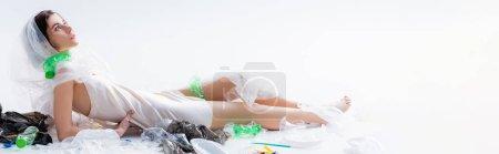 Photo pour Image horizontale de femme pieds nus en robe de soie avec sac en plastique sur la tête assis près de bouteilles vides sur blanc, concept d'écologie - image libre de droit