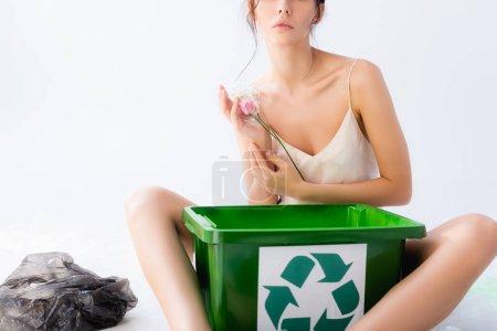 Photo pour Vue recadrée d'une femme assise près d'un sac en papier et d'une poubelle avec panneau de recyclage tout en tenant une fleur sur du blanc, concept écologique - image libre de droit