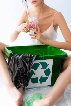 Photo for Cropped view of barefoot woman holding flower in wrap near trash can with recycle sign and plastic bag isolated on white, ecology concept - Royalty Free Image