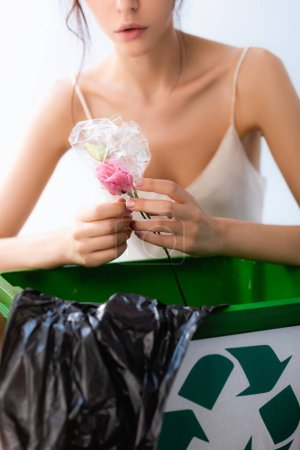 partial view of woman holding flower in wrap near trash can with recycle sign and plastic bag isolated on white, ecology concept