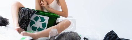 panoramic crop of barefoot woman sitting near plastic bags and trash can with recycle sign on white, ecology concept