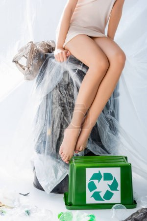 partial view of young woman in silk dress sitting on stool wrapped in plastic bag near trash bin with recycle sign on white, ecology concept