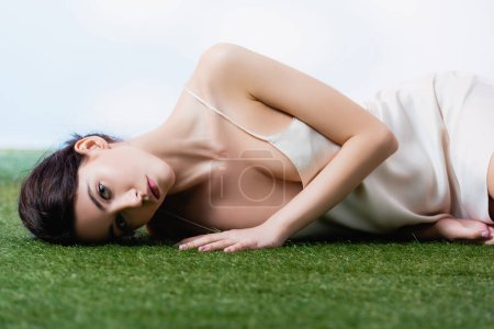 Photo for Young woman in silk dress lying on green grass on white - Royalty Free Image