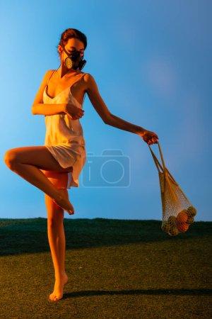 Photo pour Femme pieds nus dans un masque à gaz posant tout en tenant sac à ficelle réutilisable avec des fruits sur bleu - image libre de droit