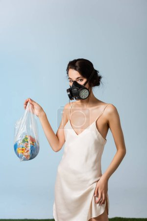 Photo for Woman in gas mask holding plastic bag with globe on grey, ecology concept - Royalty Free Image