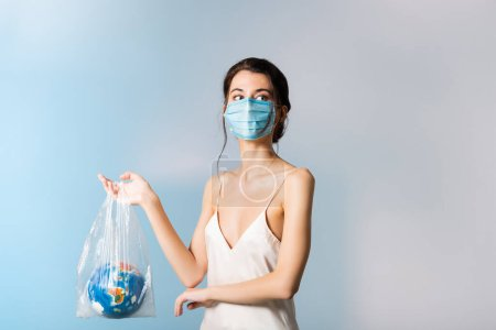 Photo for Model in medical mask holding plastic bag with globe and looking away on blue, ecology concept - Royalty Free Image