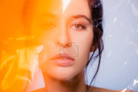 Photo pour Jeune modèle brune regardant la caméra à travers le polyéthylène sur gris, concept écologie - image libre de droit