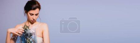 Foto de Cultivo panorámico de mujer morena sosteniendo piña en polietileno aislado en gris, concepto de ecología - Imagen libre de derechos