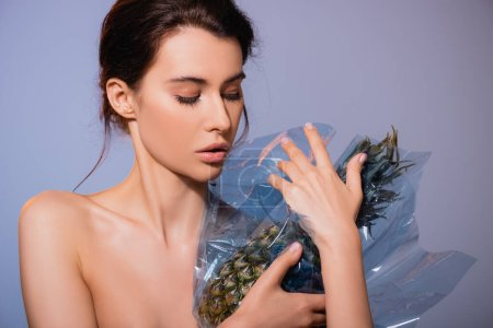 Photo for Naked brunette woman looking at pineapple in polyethylene isolated on grey, ecology concept - Royalty Free Image
