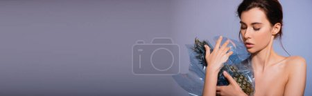 Photo for Panoramic concept of naked woman looking at pineapple in polyethylene on grey, ecology concept - Royalty Free Image