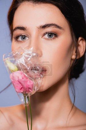 brünette Frau mit Blumen in Polyethylen isoliert auf grau, ökologisches Konzept