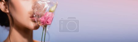 Photo pour Culture horizontale de fleurs en polyéthylène près de la jeune femme sur bleu, concept écologie - image libre de droit