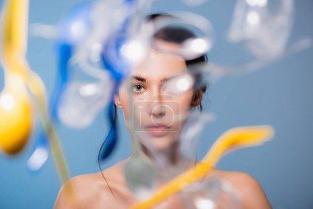 Photo pour Foyer sélectif de la femme nue près de tomber tasses en plastique, cuillères et fourchettes sur le bleu, concept d'écologie - image libre de droit