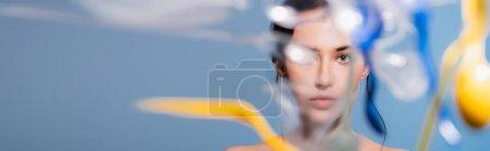 Foto de Plano panorámico de mujer desnuda cerca de caer vasos de plástico, cucharas y tenedores en azul, concepto de ecología - Imagen libre de derechos