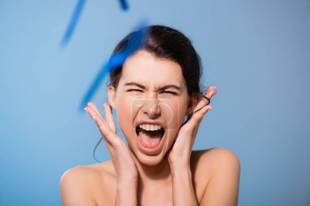 Photo for Selective focus of naked woman screaming near falling plastic forks on blue, ecology concept - Royalty Free Image