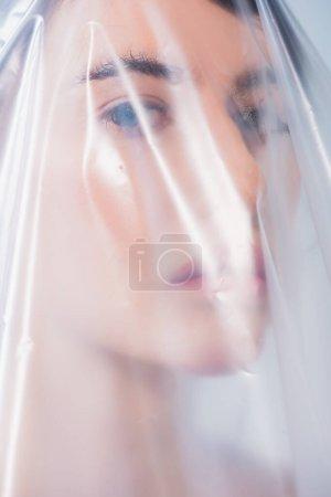 Photo pour Brunette femme recouverte de polyéthylène regardant caméra, concept d'écologie - image libre de droit