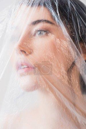 Photo pour Jeune femme brune regardant à travers le polyéthylène, concept d'écologie - image libre de droit
