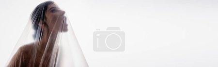 Photo for Horizontal image of brunette woman screaming through polyethylene isolated on white, ecology concept - Royalty Free Image