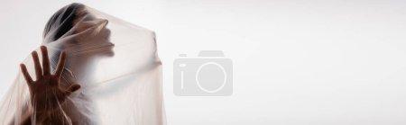plan panoramique de femme brune criant à travers du polyéthylène isolé sur du blanc, concept écologie