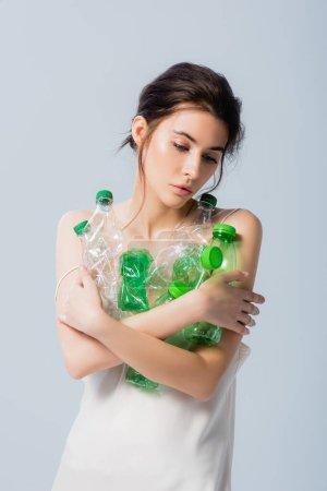 brünette Frau im Seidenkleid, Plastikflaschen in der Hand und isoliert auf graues, ökologisches Konzept herabblickend