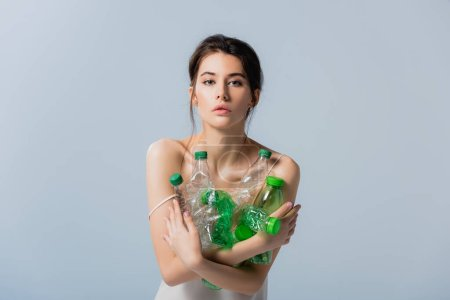 brunette woman looking at camera and holding plastic bottles isolated on grey, ecology concept