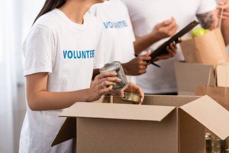 Photo pour Vue recadrée d'une femme tenant des boîtes de conserve près de bénévoles multiethniques avec presse-papiers dans un centre caritatif - image libre de droit