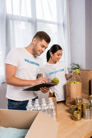 Photo for Selective focus of multiethnic volunteers writing on clipboard and holding apples near tin cans and bottles of water on table - Royalty Free Image