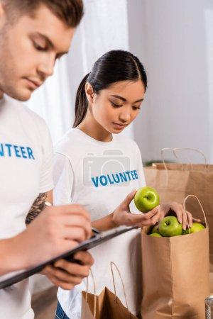 Photo pour Concentration sélective de bénévoles asiatiques tenant des pommes près de l'homme écrivant sur le presse-papiers dans un centre de bienfaisance - image libre de droit