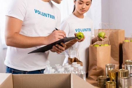 Photo pour Concentration sélective de l'écriture de l'homme sur presse-papiers près de bénévoles asiatiques tenant des pommes et des paquets dans le centre de charité - image libre de droit