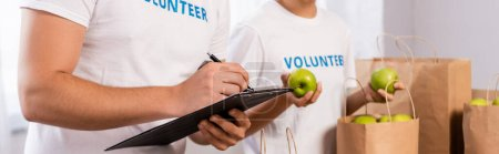 Photo for Panoramic shot of volunteers writing on clipboard and holding apples near packages in charity center - Royalty Free Image