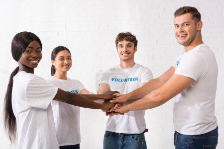 Photo pour Jeunes bénévoles multiculturels tenant la main tout en regardant la caméra dans un centre de bienfaisance - image libre de droit