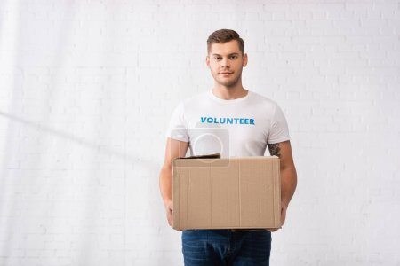 Volunteer with lettering on t-shirt looking at camera while holding carton package