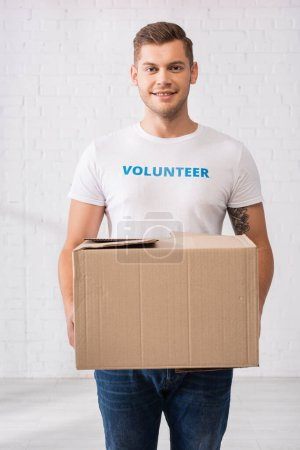 Photo pour Volunteer in white t-shirt holding cardboard package in charity center - image libre de droit