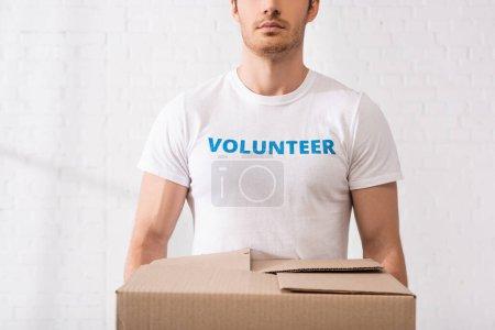 Ausgeschnittene Ansicht von Freiwilligen im T-Shirt mit Schriftzug in Kartonschachtel