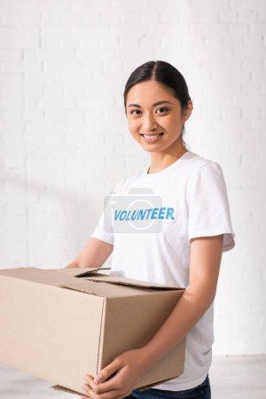 Asiatischer Freiwilliger schaut in Kamera, während er Karton hält