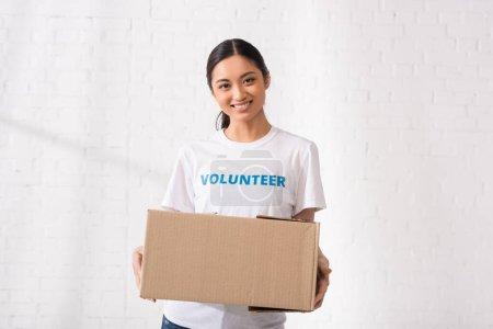 Photo pour Volontaire asiatique avec lettrage sur le paquet de tenue de t-shirt dans le centre de charité - image libre de droit