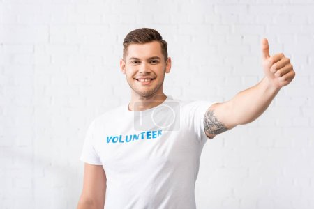 Photo pour Volontaire en t-shirt avec lettrage montrant pouce vers le haut - image libre de droit