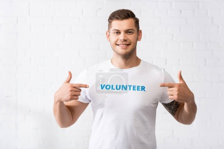 Photo for Young volunteer pointing at lettering on white t-shirt and looking at camera - Royalty Free Image