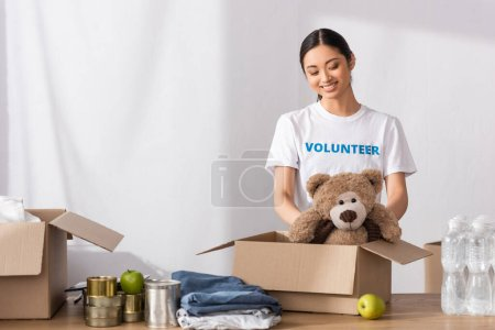 Asian volunteer putting soft toy in carton package near clothes and tin cans in charity center