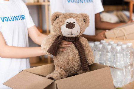 Photo for Cropped view of volunteer putting soft toy in carton box near packages with bottles of water in charity center - Royalty Free Image