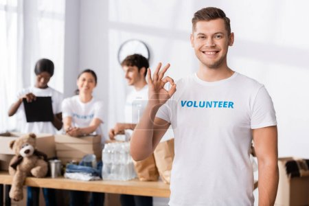 Photo for Selective focus of volunteer showing okay gesture at camera in charity center - Royalty Free Image