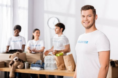Selective focus of volunteer looking at camera in charity center