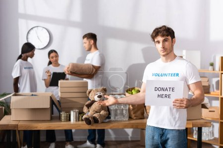 Photo pour Jeune bénévole pointant avec la main tout en tenant la carte avec faire un don ici lettrage dans le centre de charité - image libre de droit