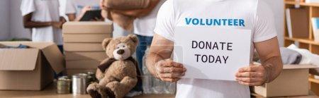 Photo pour Photo panoramique de la carte de maintien des bénévoles avec faire un don aujourd'hui lettrage dans le centre de bienfaisance - image libre de droit