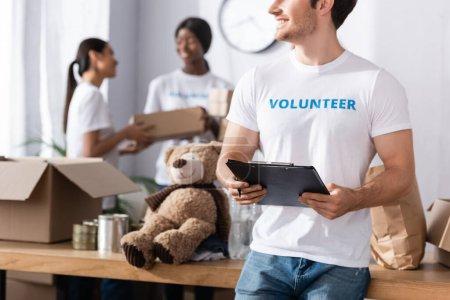 Photo pour Concentration sélective du bénévolat tenant presse-papiers et stylo dans le centre de charité - image libre de droit