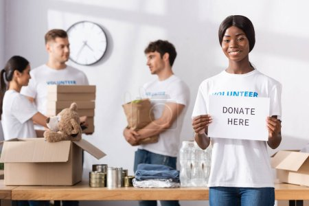 Photo pour Focalisation sélective du volontariat afro-américain tenant la carte avec faire un don ici lettrage - image libre de droit
