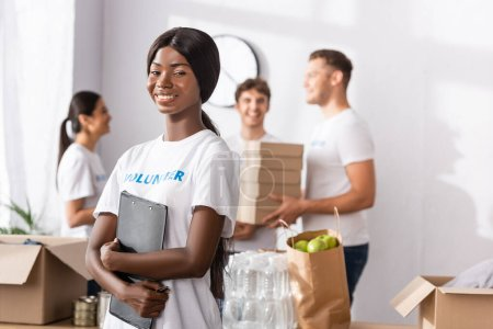 Photo for Selective focus of african american volunteer holding clipboard near donations in charity center - Royalty Free Image