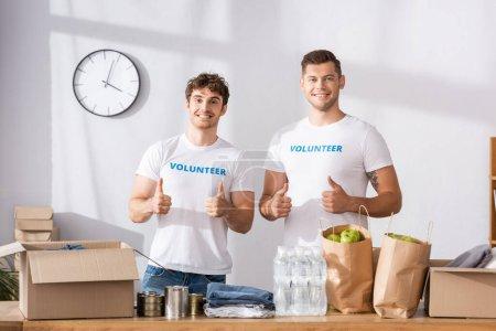 Photo pour Bénévoles montrant pouces vers le haut près des paquets et des vêtements sur la table dans le centre de charité - image libre de droit